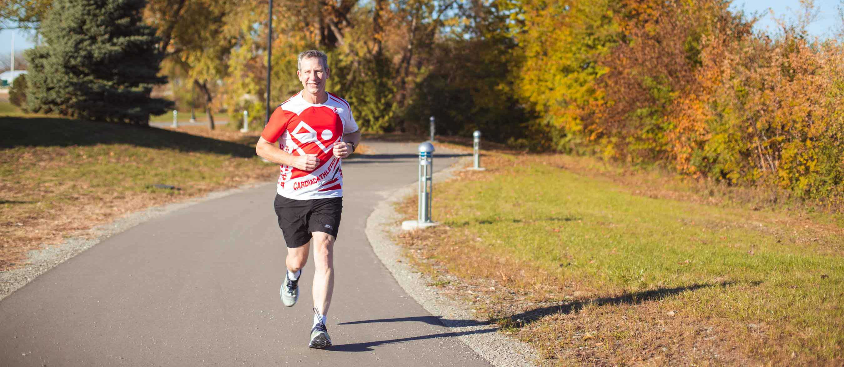 White man running outside on a paved trail in fall