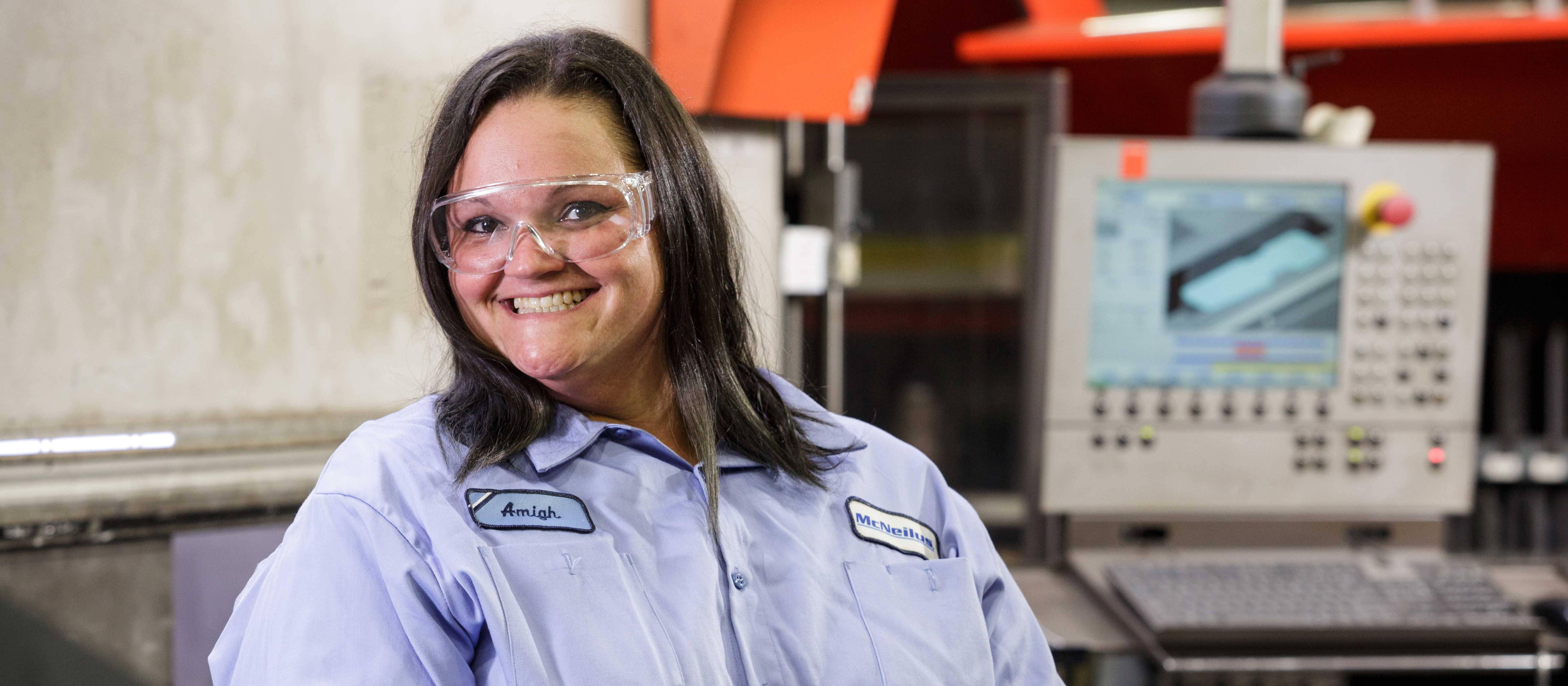 Woman with dark brown hair standing in a production facility smiling in a blue button up McNeilus shirt